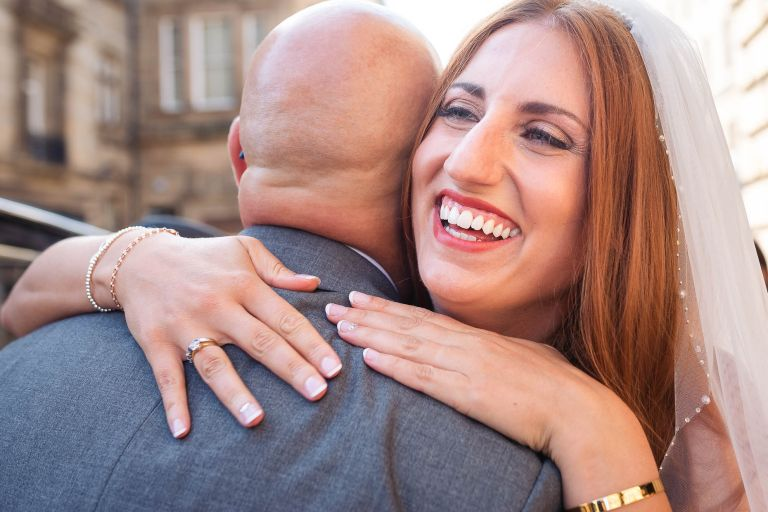 Bride laughs as she gives her father a hug
