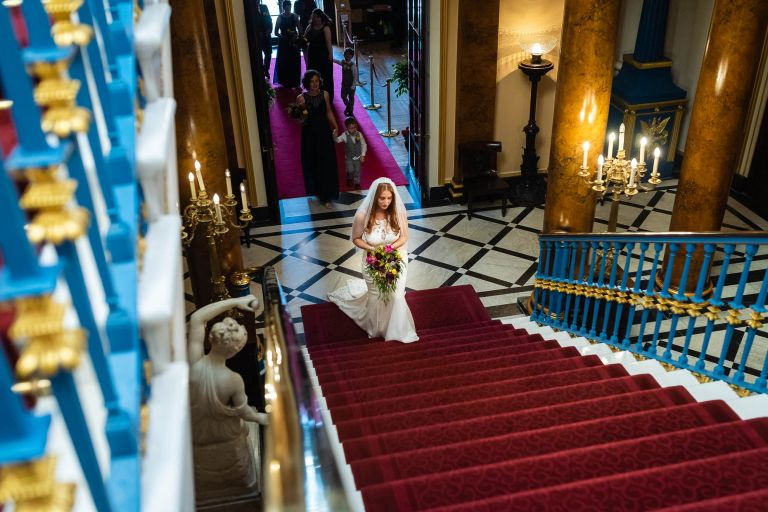 Bride walks up town hall stairs