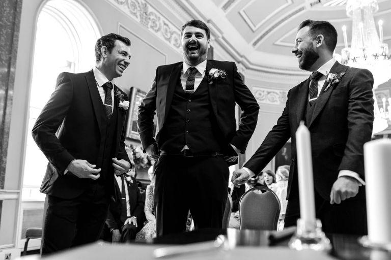 Groom shares a joke with his groomsmen