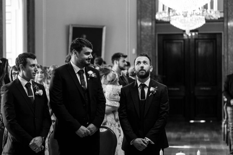 Groom looks nervous as he waits for his bride