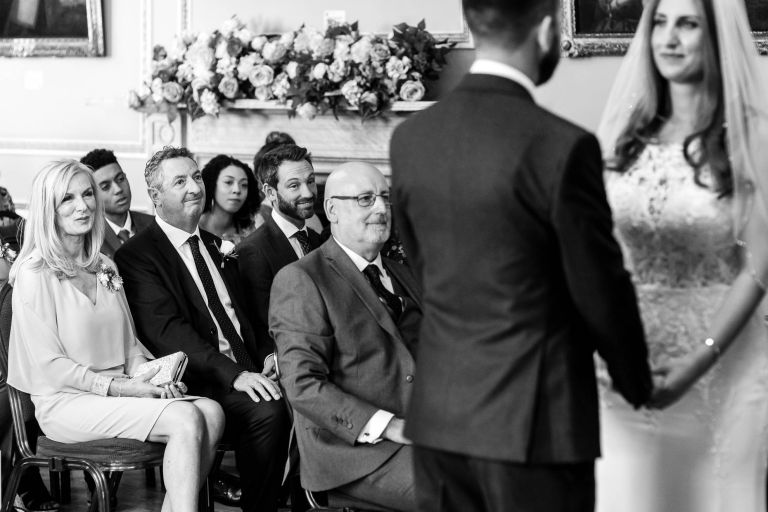 Mother of the bride an stepfather look on as bride and groom say vows