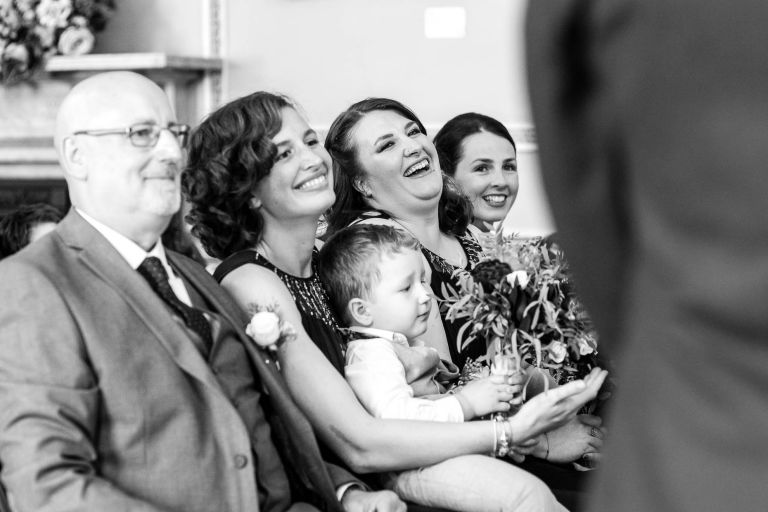 Bridesmaids share a joke during the ceremony