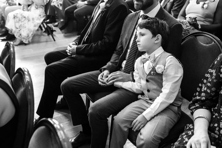Page boy looks on during the vows