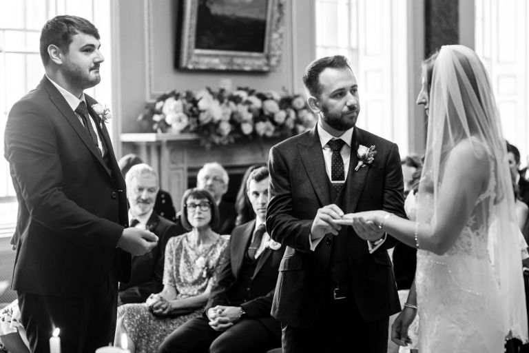 Groom places ring on brides finger