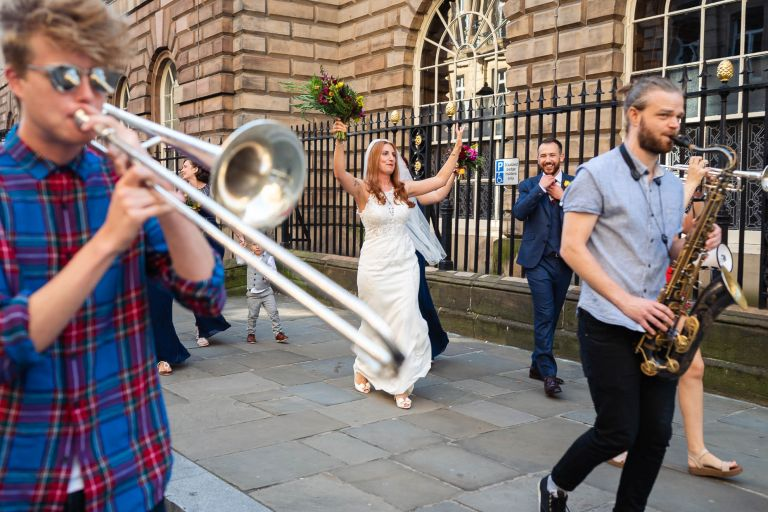 Bride dancing along street while a brass band is playing