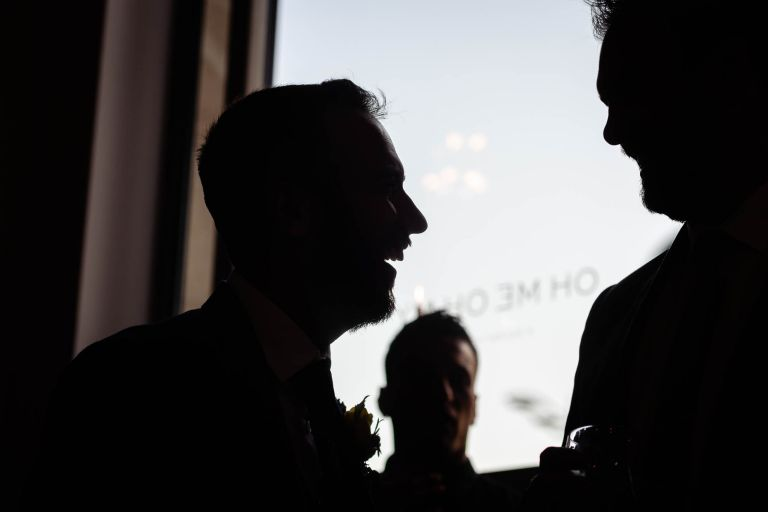 silhouette of groom with guest