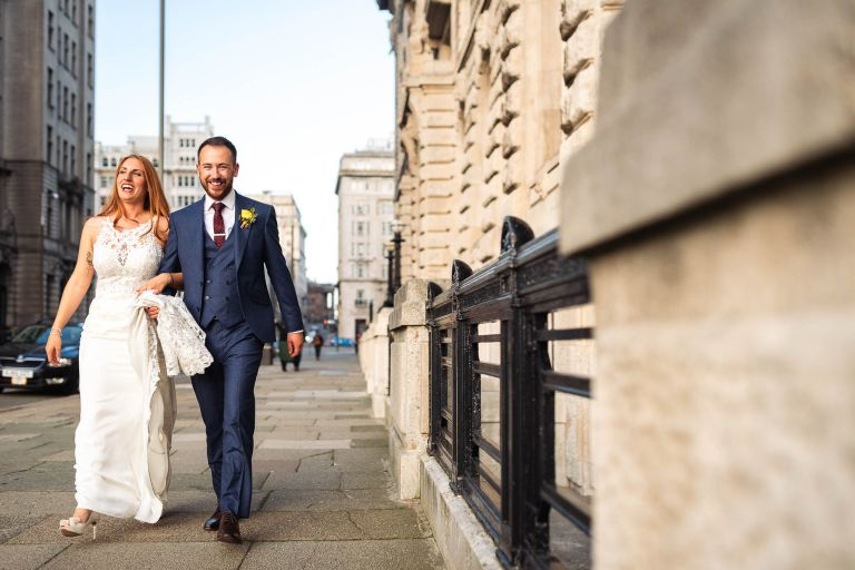 Bride and groom share a joke as they walk around the Three Graces in liverpool