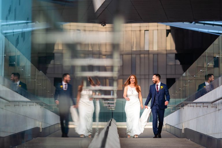 Bride and groom share a joke as they walk past museum