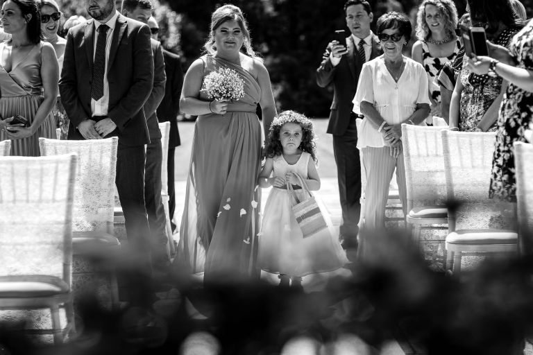 Flower girl looking anxious as she walks up the aisle