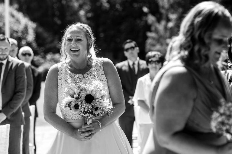 Bride smiles at the groom as she walks up the aisle