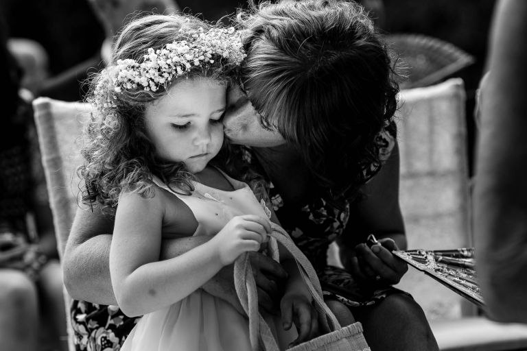 Flower girl gets a kiss from her mother