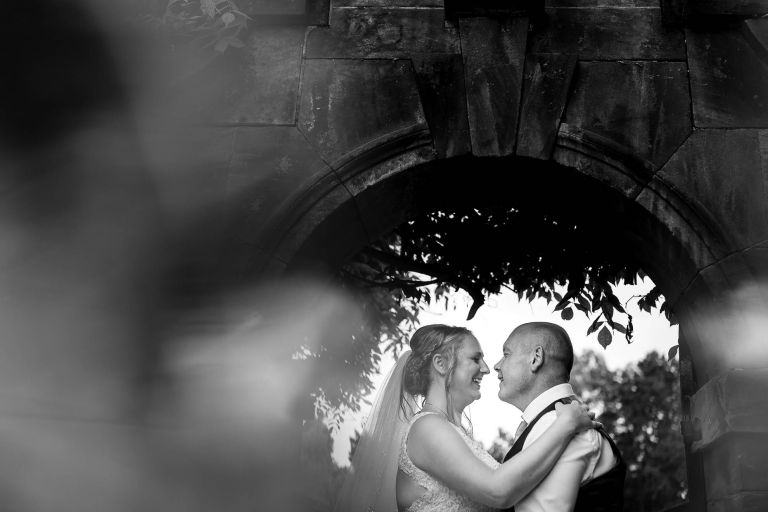 Bride and groom portrait under arch
