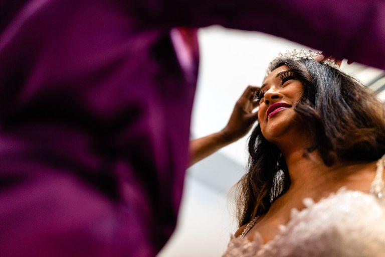 Bridesmaid places tiara on brides head