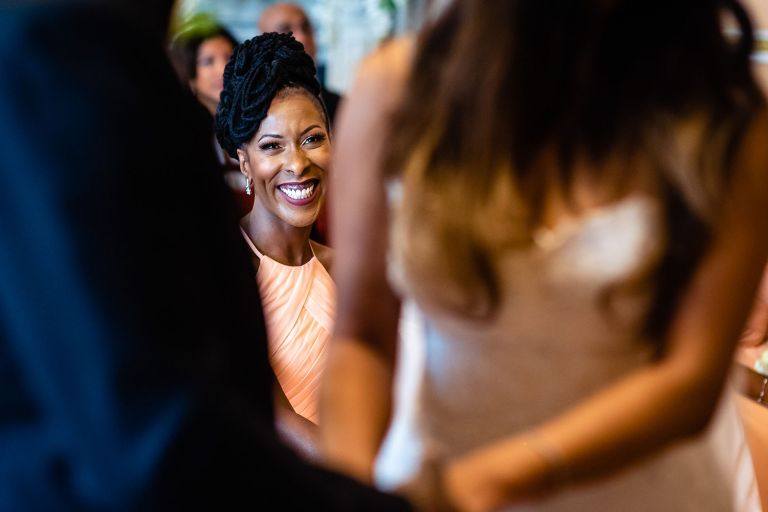 Bridesmaid looks on smiling during the exchange of vows