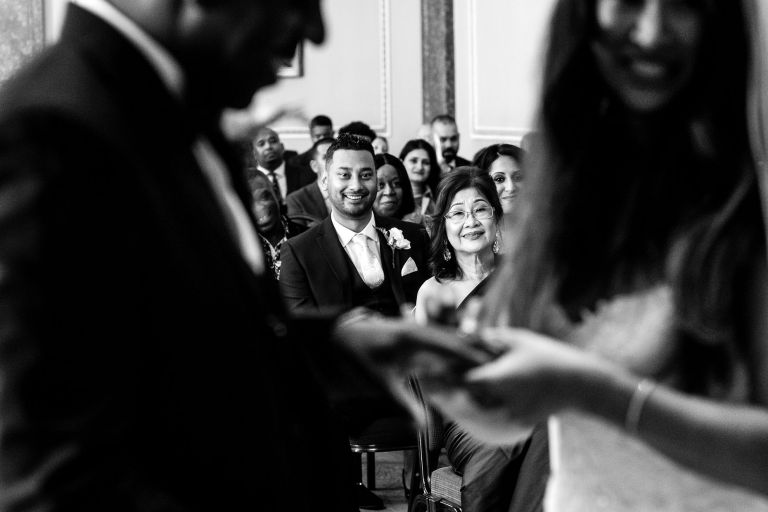 Mother of the bride and brother watch the exchange of rings