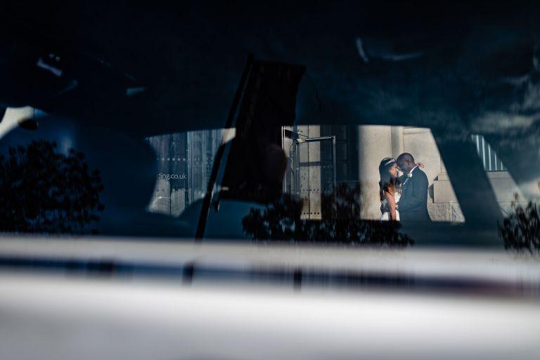 Bride and groom portrait through wedding car window