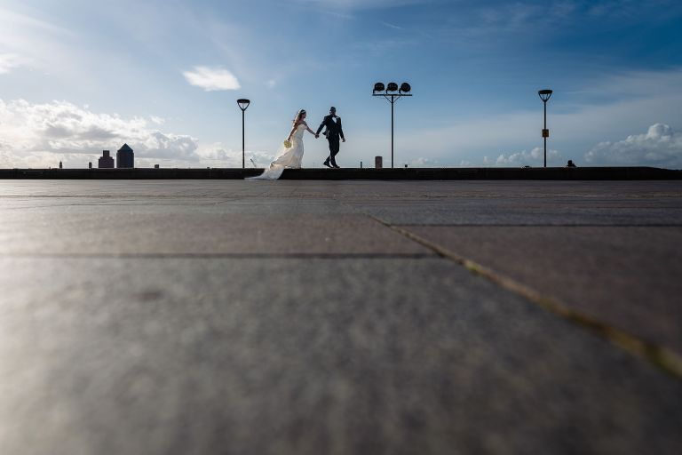 Bride and groom walking together along waterfront