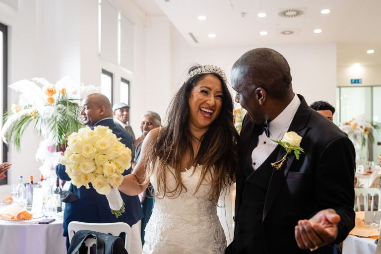 Bride and groom share a joke as they enter the wedding breakfast