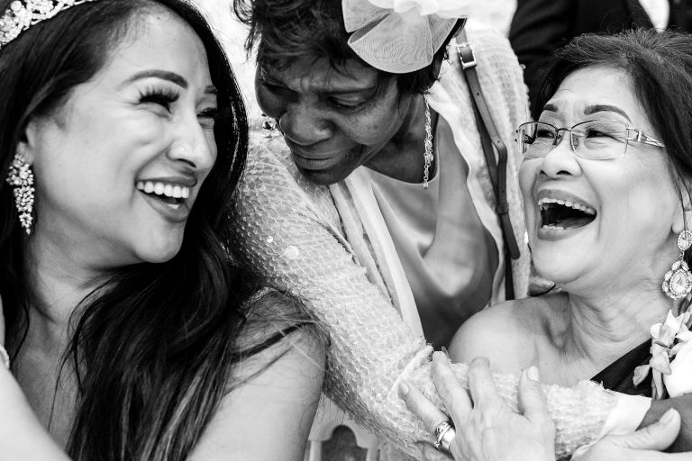 Bride and mother of the bride share a joke with guest