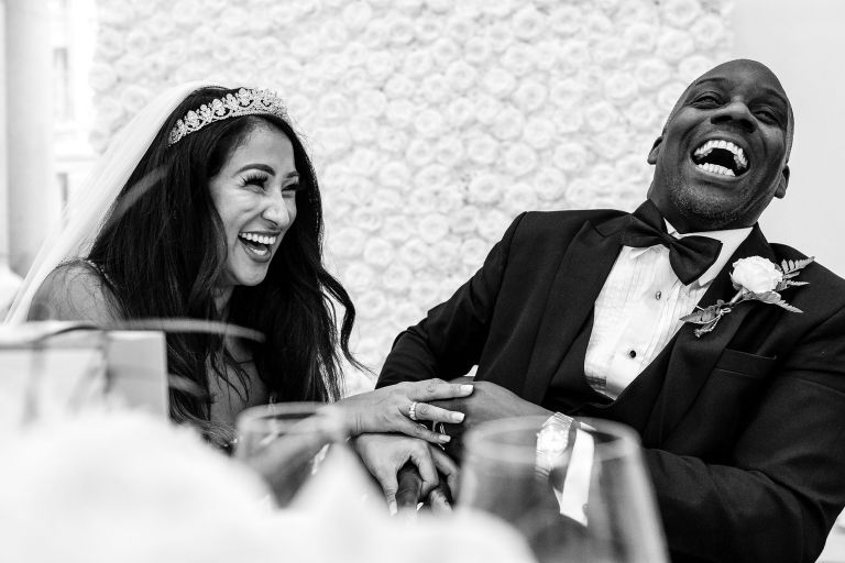 The happy couple laugh at guests joke
