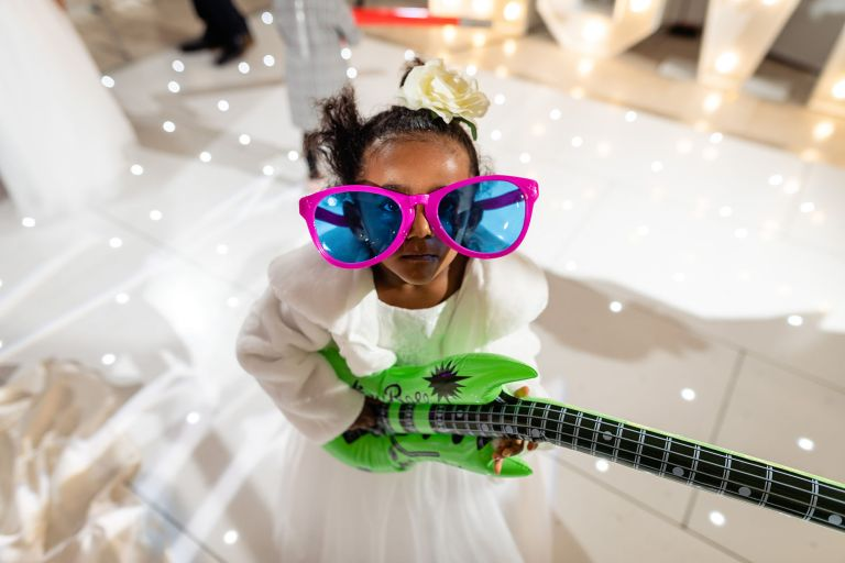 Flower girl with toy guitar and huge sunglasses
