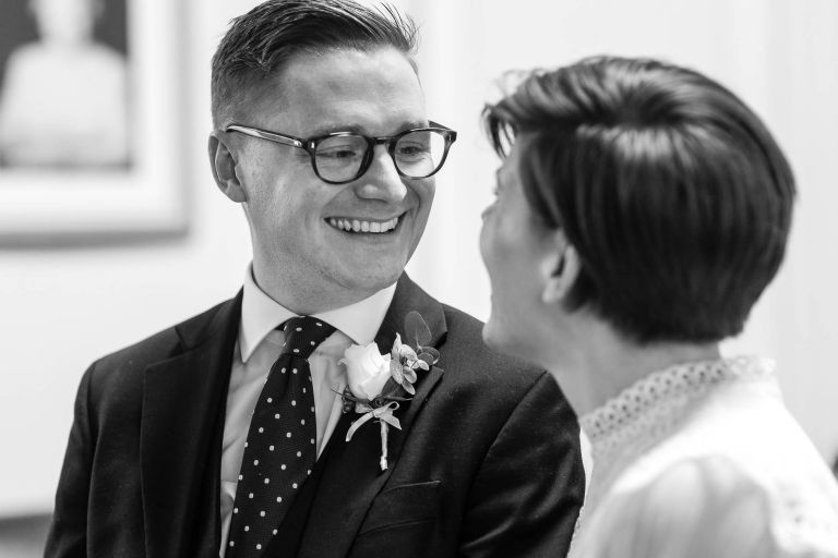 groom smiles at bride during exchange of vows