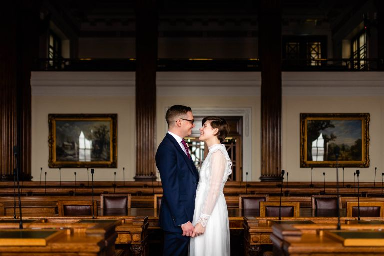 Bride and groom hold each other in council chambers