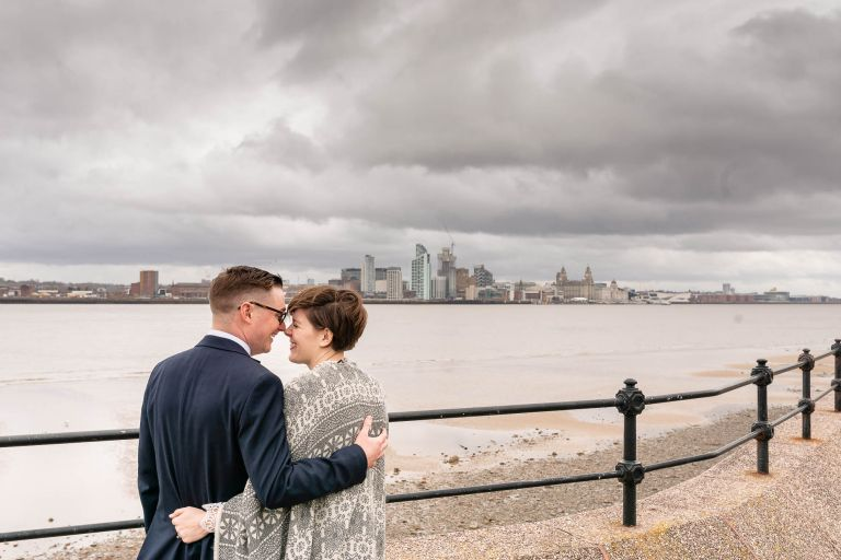 Happy couple look across the Mersey to liverpool skyline