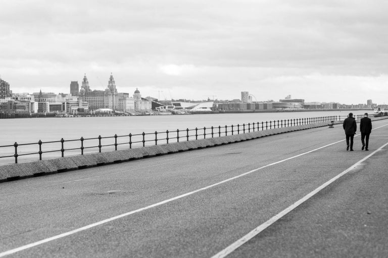 Groom and best man walk down Mersey waterfront