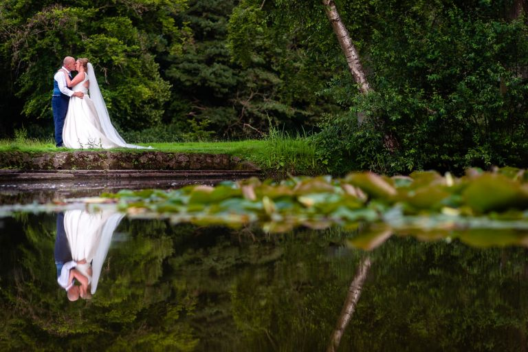 Bride and groom portrait reflection in lake